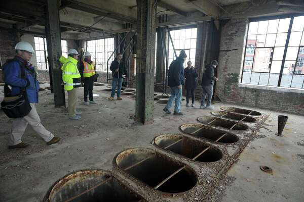 Environmental contractors tour the historic Remington Arms factory in Bridgeport, Conn., in January 2020. The administration of Gov. Ned Lamont is aiming to update the state's Property Transfer Program.