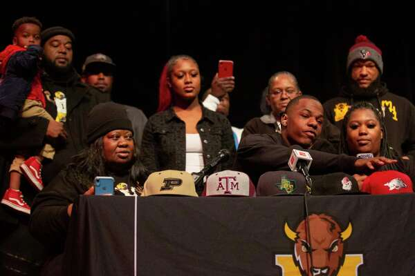 Thurgood Marshall High School student Malik Hornsby picks the hat of Arkansas Razorbacks surrounded by his family on National Signing Day on Wednesday, Feb. 5, 2020, in Missouri City.