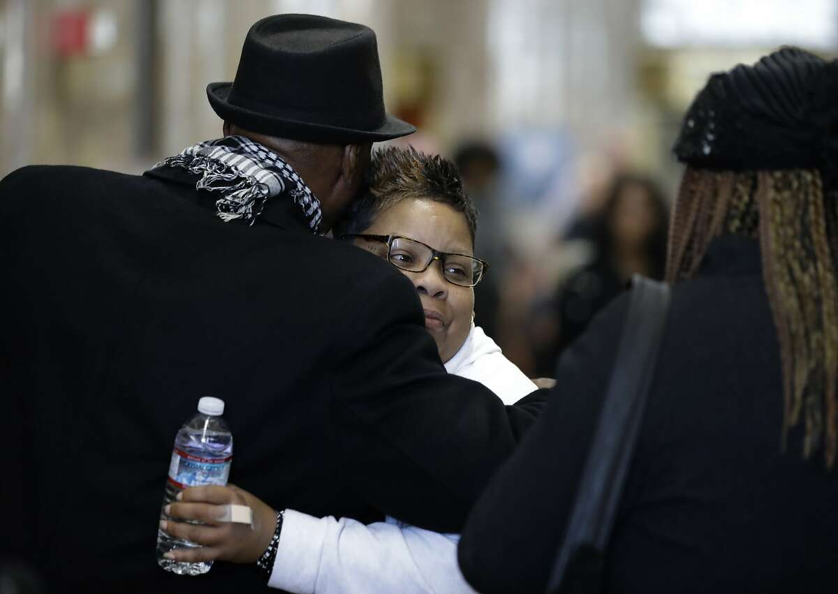 Alicia Grayson, the mother of Nia Wilson, is embraced after speaking with reporters in a courthouse lobby Wednesday, Feb. 5, 2020 in Oakland, Calif. The family of Nia Wilson appeared in court for opening statements in the trial of John Lee Cowell, who is charged with murder for the fatal stabbing of 18-year-old Nia Wilson at the MacArthur BART station in Oakland in 2018. (AP Photo/Ben Margot)