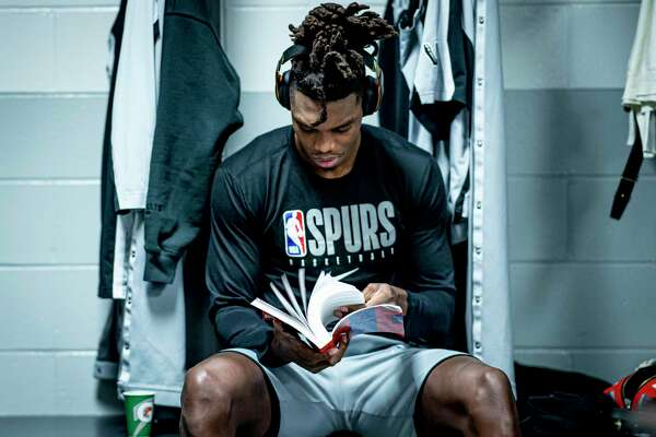 San Antonio Spurs guard Lonnie Walker IV reads a book in the locker room before the game against the Boston Celtics at the TD Garden in Boston, Massachusetts Wednesday, January 8, 2020.