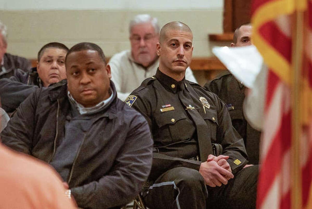 Alton's Director of Development and Housing Greg Caffey, left, and Alton Deputy Police Chief Marcos Pulido, right, listen to Mayor Brant Walker deliver is State of the City address Tuesday night at the Spaulding Club.