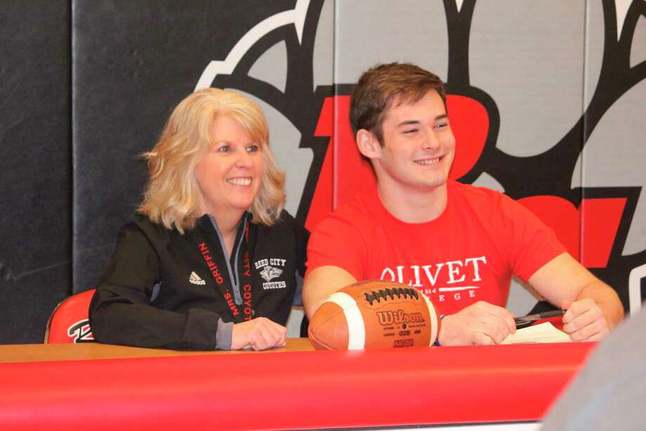 Reed City athletic director Kris Griffin (left) congratulates Coyote athlete Austin Fowler on his decision to play football and run track at Olivet College. (Pioneer photo/John Raffel)