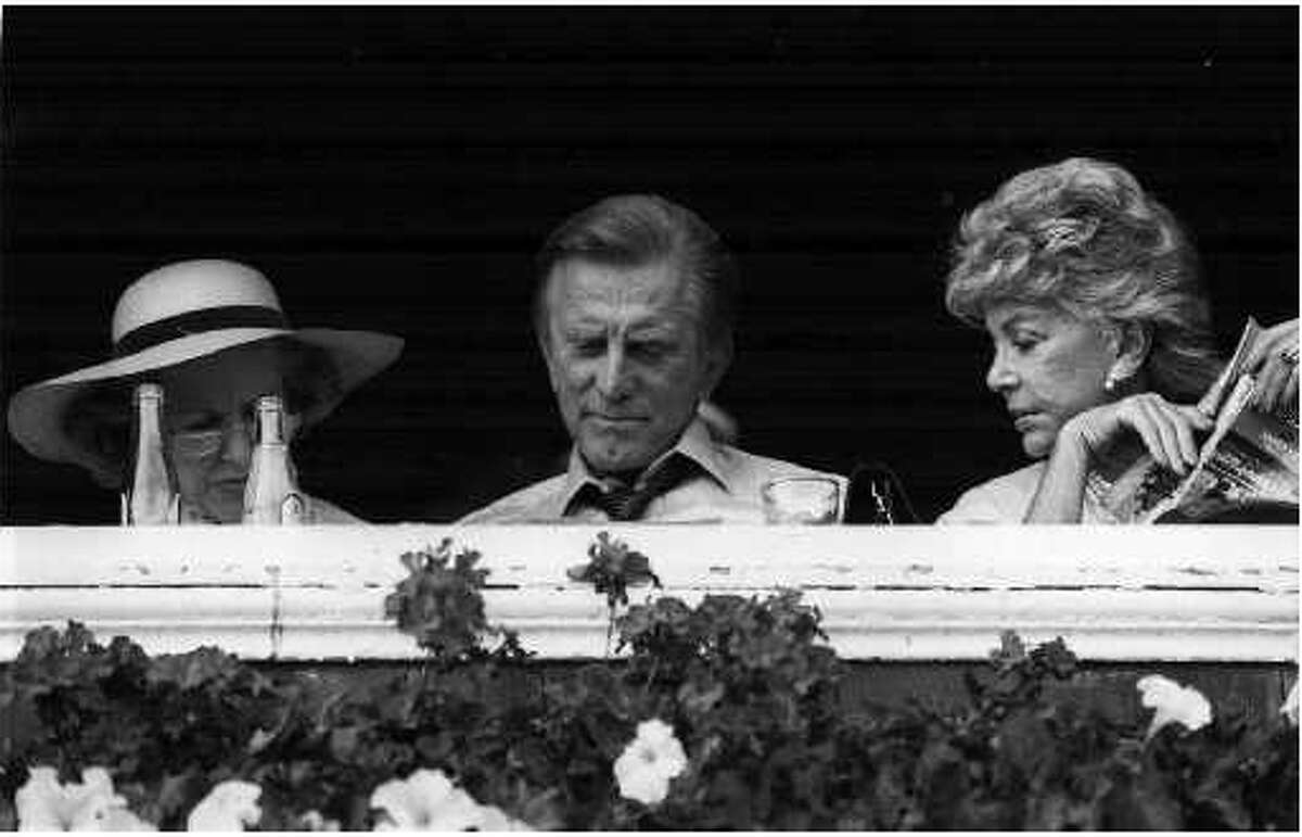 A 1985 photo of Kirk Douglas and his wife, visiting Marylou Whitney at the Saratoga Race Course. From the New York Racing Association collection