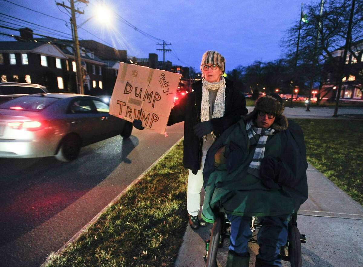 """Pat Ferris of Old Greenwich and her son Joe Edelstein stand along Field point Avenue as a rally outside Greenwich Town Hall takes place in Greenwich, Conn. on Feb. 5, 2020. Over 100 participants gather with members of Indivisible Greenwich to hold a """"peaceful assembly"""" Tuesday night to demonstrate solidarity in what it calls rising authoritarianism."""