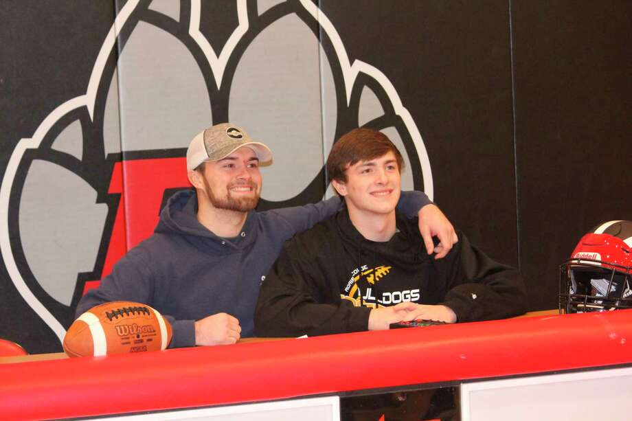 Chad Samuels (left), a former Reed City and Northwood football player, congratulates his younger brother, Jeffrey, for signing a letter on Wednesday to play football at Adrian College. (Pioneer photo/John Raffel)