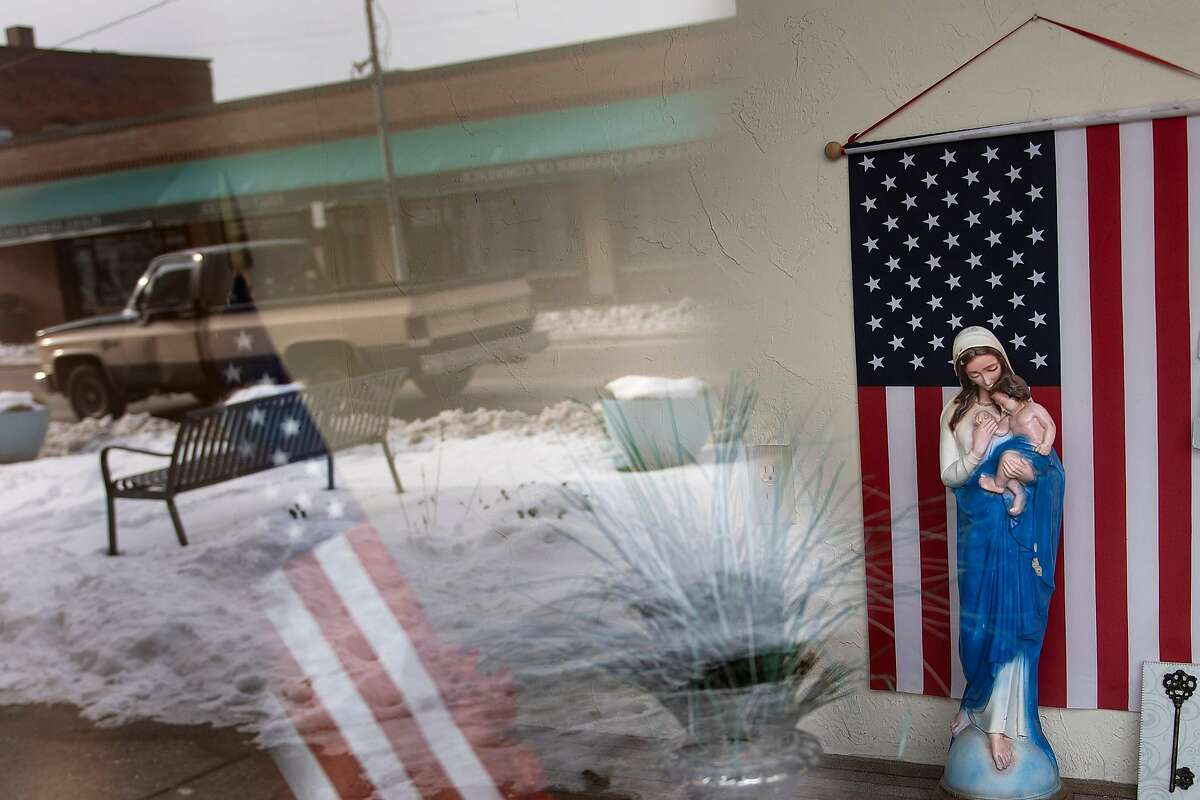A storefront is seen with American flags and a statue of Marry on Main Avenue January 22, 2020, in Ashtabula, Ohio. - America is in flux. Once stable jobs have become precarious, mass media that united have turned to cacophony, and communities that once appeared monolithic have been transformed by diversity. After driving nearly 3,000 kilometers across the United States, an AFP team has found consensus on at least one point this years election will be pivotal. (Photo by Brendan Smialowski / AFP) (Photo by BRENDAN SMIALOWSKI/AFP via Getty Images)