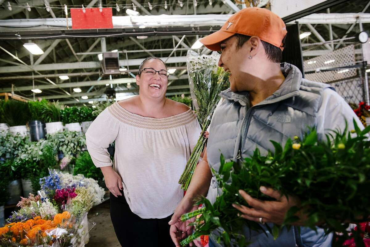 Interior designers Heather Hughes, right, and Sophia Calvia share a laugh as they shop for flowers at Piazza Wholesale inside the San Francisco Flower Mart in San Francisco, Calif, on Monday, September 30, 2019.