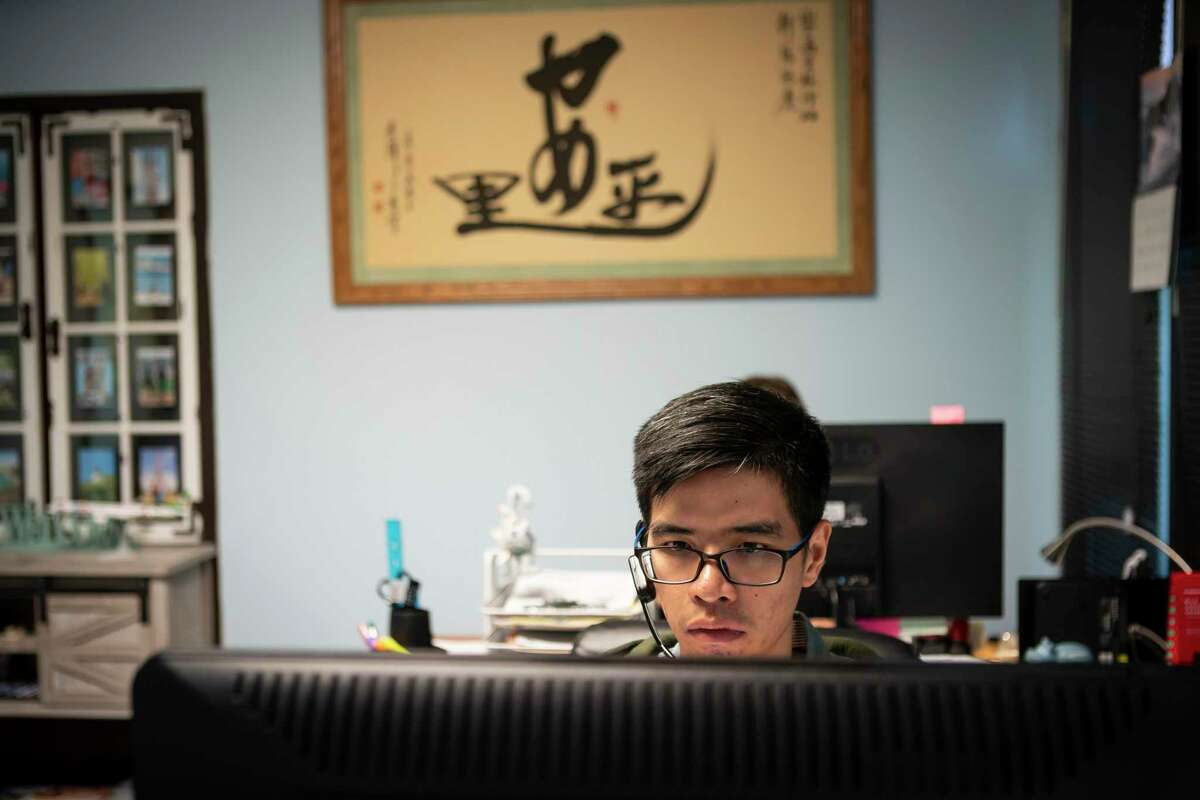 Dylan Li, manager at Pally Travel Services, Inc., works in his office Wednesday, Feb. 5, 2020, in Houston. Li has watched his business, 90 percent of which involves travel to China, severely drop in the past month.