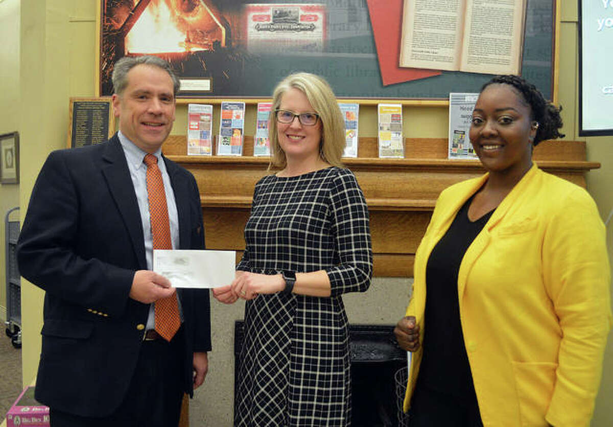 Dave Toby, left, senior vice president of FCB Banks in Edwardsville, hands a check for $2,500 to Edwardsville Public Library Director Schardt as Brejani Owens, the library's new social work intern from SIUE, looks on. The money from FCB Banks will help pay for an MSW (a person with a master's degree in social work) to supervise Owens' practicum.