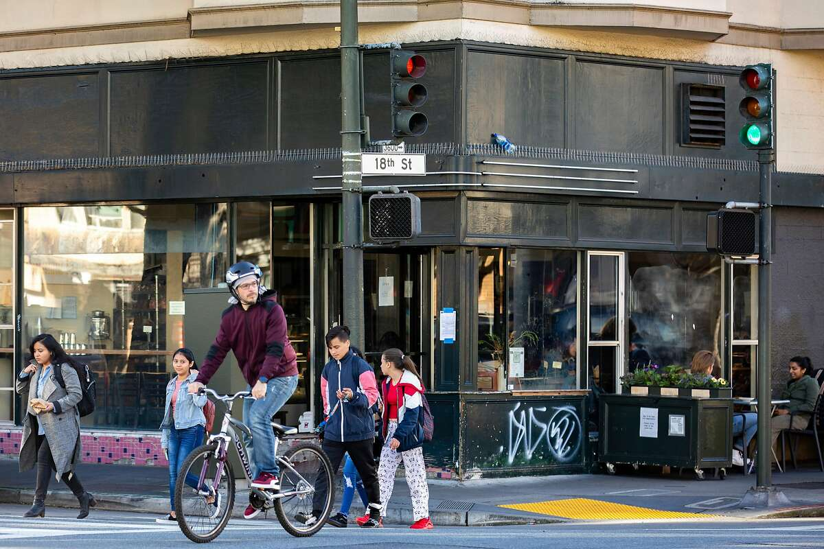 People make their way past Tartine Bakery, located at 600 Guerrero St., Wednesday, Feb. 5, 2020, in San Francisco, Calif.