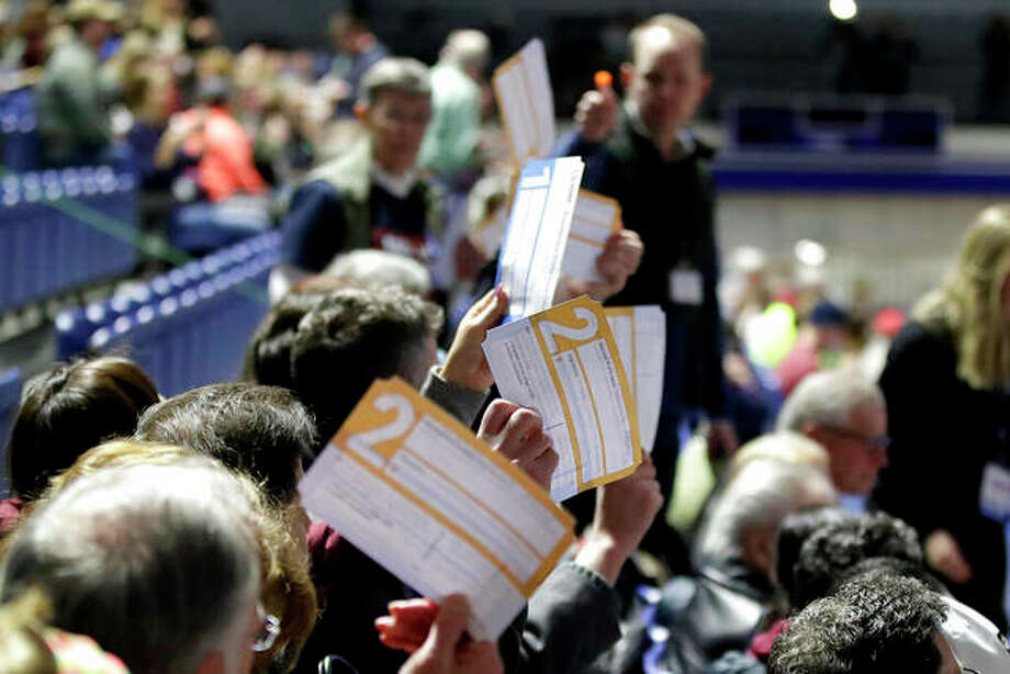 Caucus goers seated Monday in the section for Democratic presidential candidate and former Vice President Joe Biden hold up their first votes as they are counted at the Knapp Center on the Drake University campus in Des Moines, Iowa. Photo: Gene J. Puskar | AP