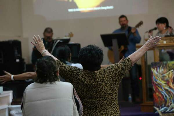 Pastor Rosie Gonzales, 76, center, joins in the singing during service at Liberty Christian Church in Cotulla. Gonzales started the congregation in 1990. It occupies a former five-and-dime store on historic North Front Street.