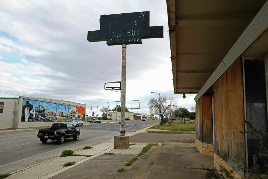 Traffic is light at the corner of Main Street and Texas 97 in Cotulla. Before the slowdown in the Eagle Ford Shale, the intersection was busy with oil-field-related traffic. The old Amberson Building, right, is vacant and boarded up. At the height of the fracking boom, an oil-related company leased part of the first floor. Photo: Jerry Lara / **MANDATORY CREDIT FOR PHOTOG AND SAN ANTONIO EXPRESS-NEWS/NO SALES/MAGS OUT/TV   © 2019 San Antonio Express-News