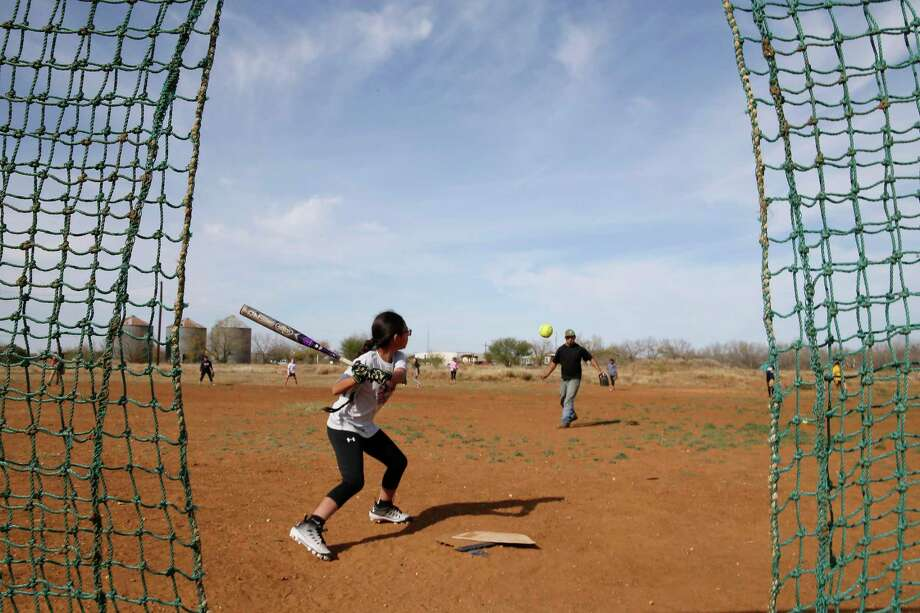 The Lil Storm 12U softball team practices in a field that used to house an oil-field service company in Cotulla. Photo: Jerry Lara / **MANDATORY CREDIT FOR PHOTOG AND SAN ANTONIO EXPRESS-NEWS/NO SALES/MAGS OUT/TV   © 2019 San Antonio Express-News
