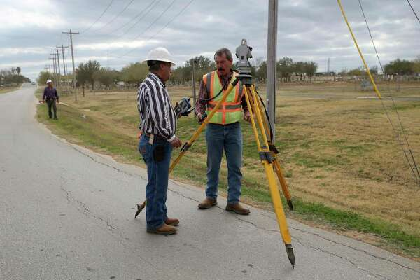 Erasmo Solano, 52, center, Marco Garcia, 57, right, and Ricardo Lopez, 36, on the left, prepare to survey land along North Baylor Street in Cotulla, Texas, Wednesday, Jan. 8, 2020. They were surveying the land for a parking lot at a school construction site. Behind them, a lot that once housed trailer homes for oil-field related workers is empty.
