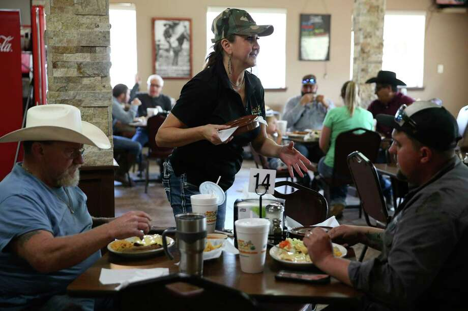 Jackie Almendarez, 53, serves Stan Jones, 53, left, and Todd Bartels, 29, at Agave Jalisco Mexican Restaurant in Tilden. The town, along with others in the Eagle Ford Shale, has seen a slowdown in the oil-field-related busness. Photo: Jerry Lara / **MANDATORY CREDIT FOR PHOTOG AND SAN ANTONIO EXPRESS-NEWS/NO SALES/MAGS OUT/TV   © 2019 San Antonio Express-News
