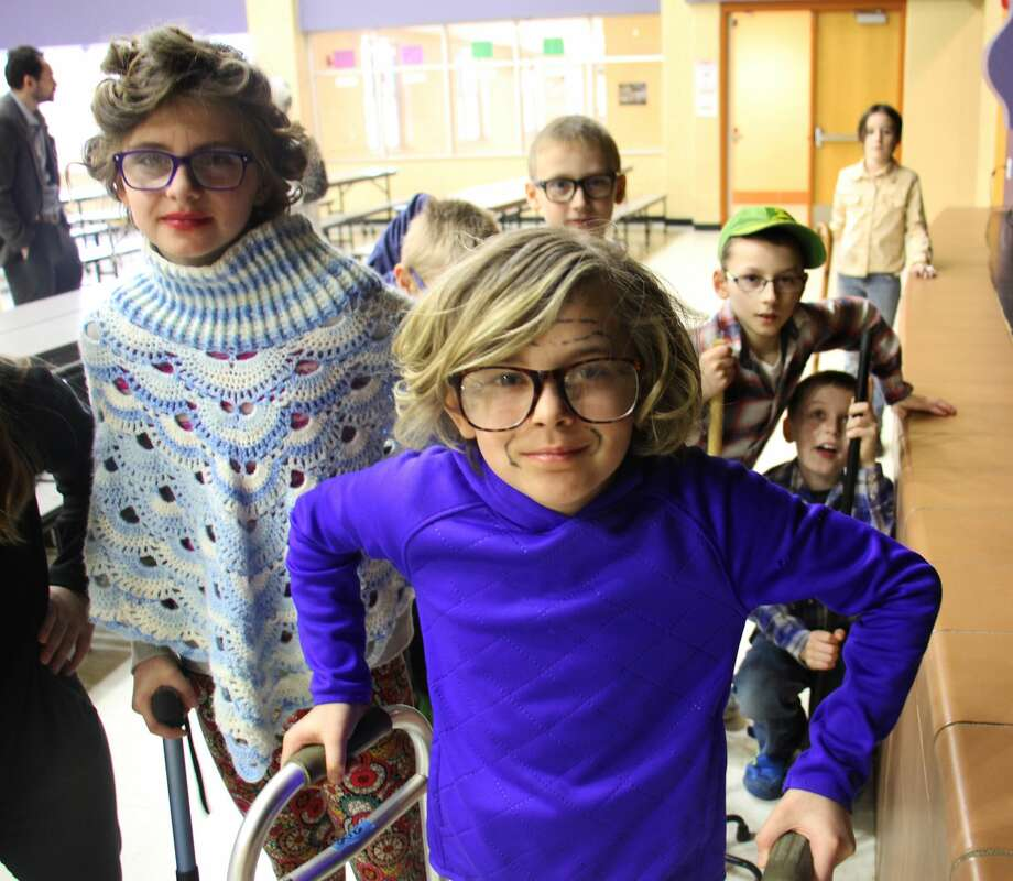 Addyson Pfaf and Avery Gonzales of the fourth grade have fun dressing up as elderly women. Photo: Sara Eisinger/Huron Daily Tribune