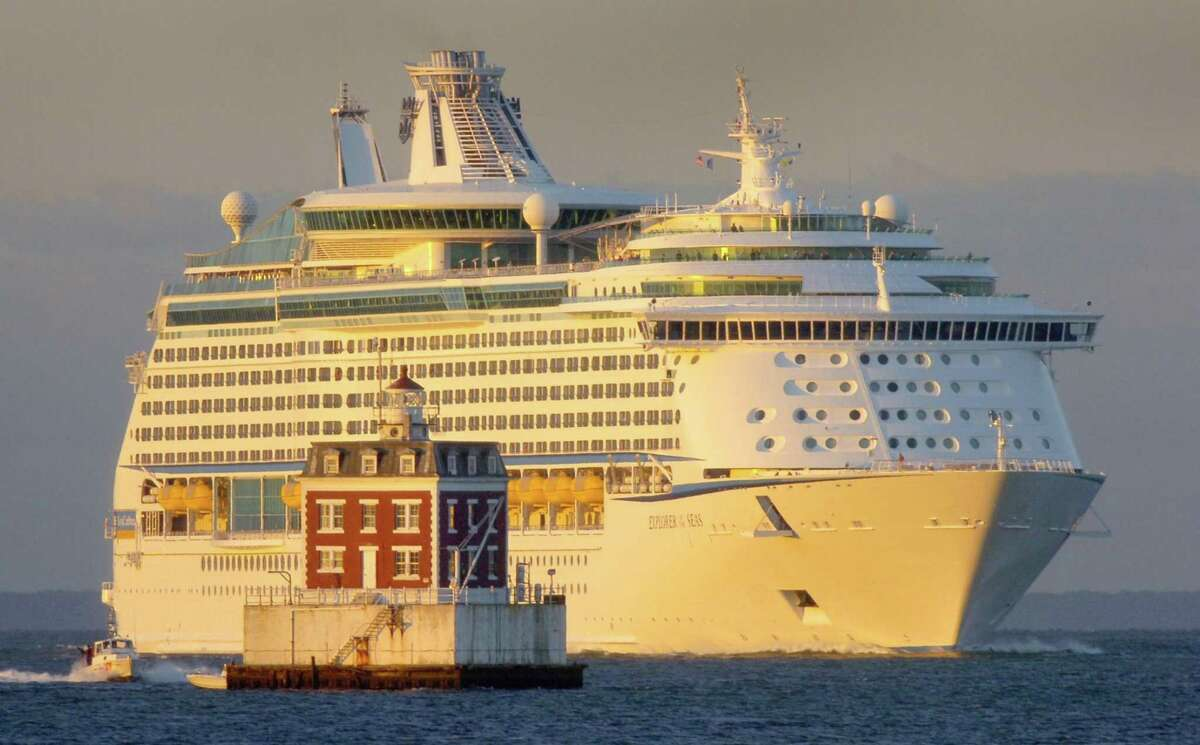 The Royal Caribbean International cruise ship Explorer of the Seas is lit by the sunrise as it passes New London Ledge Lighthouse in Groton, Conn., Saturday Sept. 1, 2007. (AP Photo/The Day, Tim Cook) ** MAGS OUT, NO SALES, INTERNET OUT, MANDATORY CREDIT **