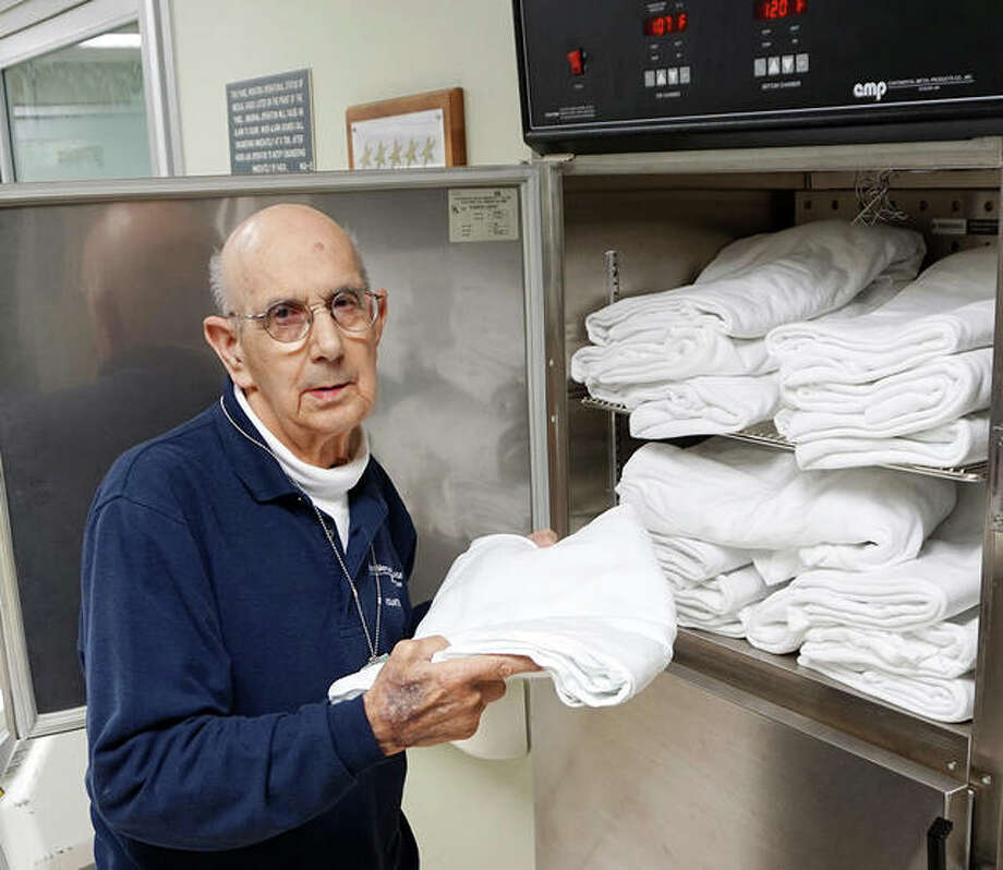 Carl Draper, of Wood River, fills the blanket warmer in the Alton Memorial Hospital Emergency Room in a 2018 photo. Draper, who logged more than 40,000 volunteer hours at the hospital, died Jan. 30.