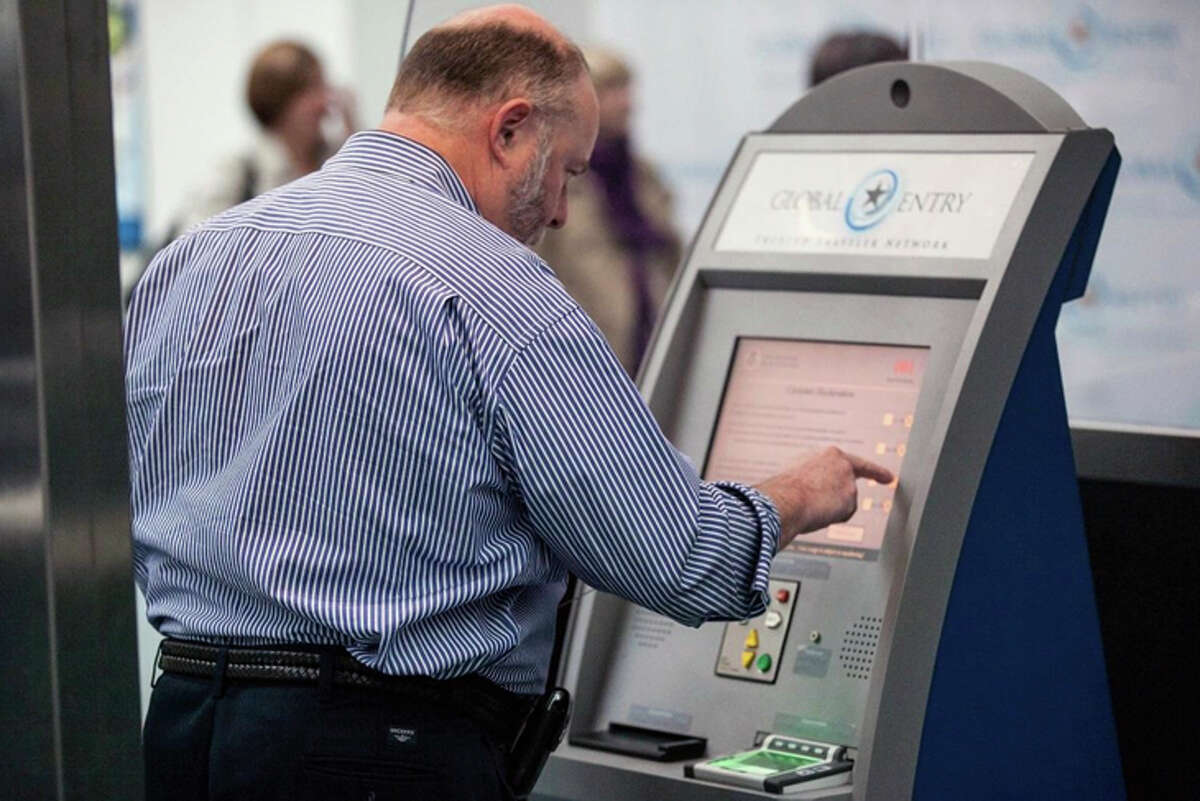 A returning traveler at an airport Global Entry kiosk.