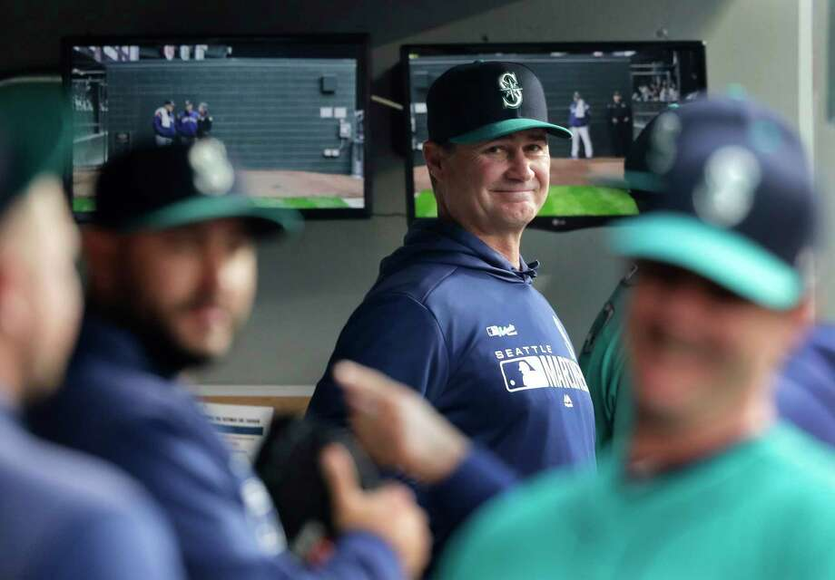 FILE - In this April 12, 2019 file photo, Seattle Mariners manager Scott Servais, center, smiles in the dugout before a baseball game against the Houston Astros in Seattle. Spring training for the Mariners ahead of the 2020 season will feature young players and prospects that could be at the heart of whether the Mariners' rebuild plans ultimately work. Photo: Ted S. Warren, AP / Copyright 2019 The Associated Press. All rights reserved.