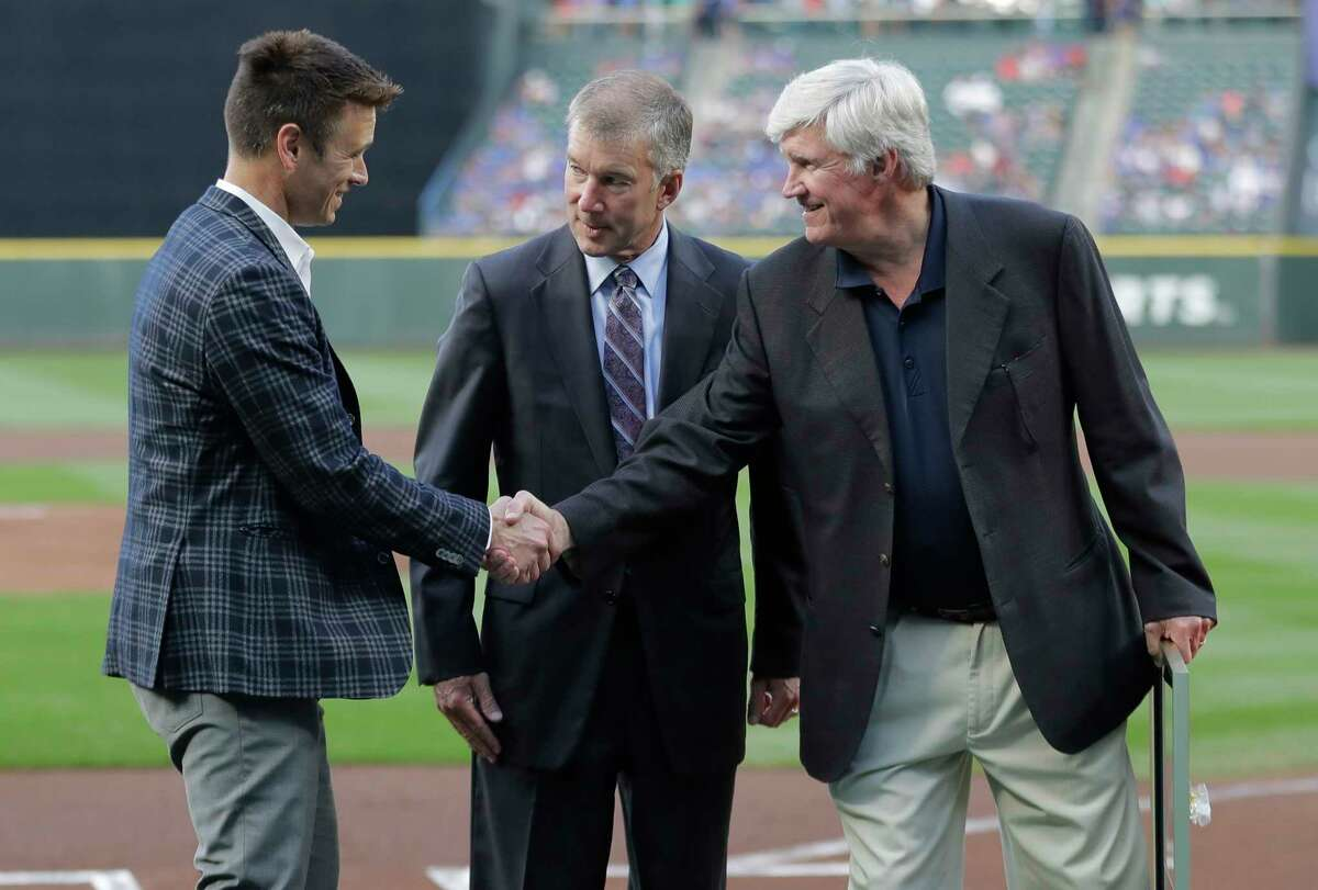 FILE - In this Aug. 3, 2018 file photo, Seattle Mariners general manager Jerry Dipoto, left, President Kevin Mather, center, and owner John Stanton, right, take part in a ceremony before a baseball game against the Toronto Blue Jays in Seattle. Spring training for the Mariners ahead of the 2020 season will feature young players and prospects that could be at the heart of whether the Mariners' rebuild plans ultimately work.