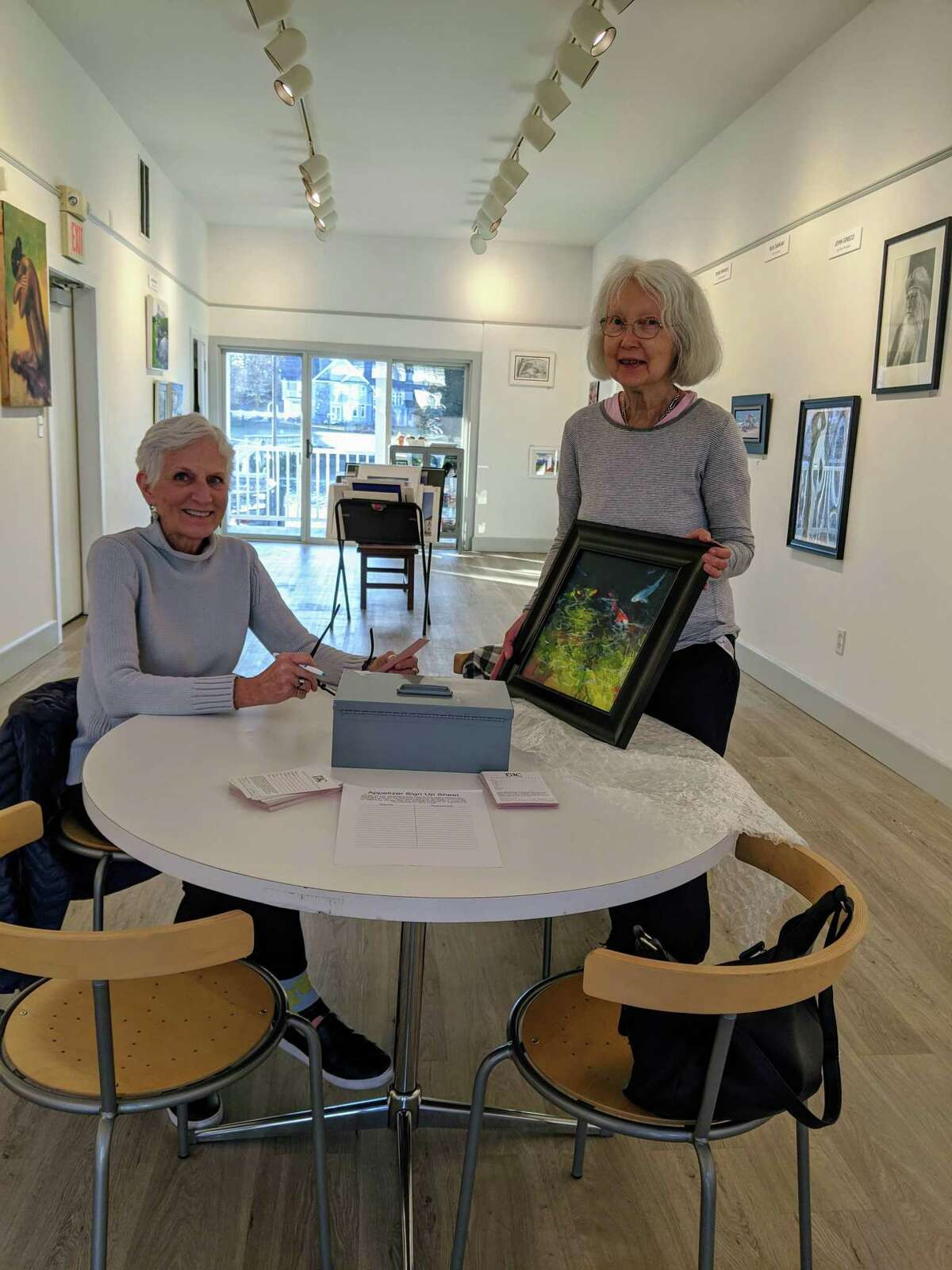 Laure Dunn, left, receives a painting by Virginia Jennewein at Rowayton Arts Center.