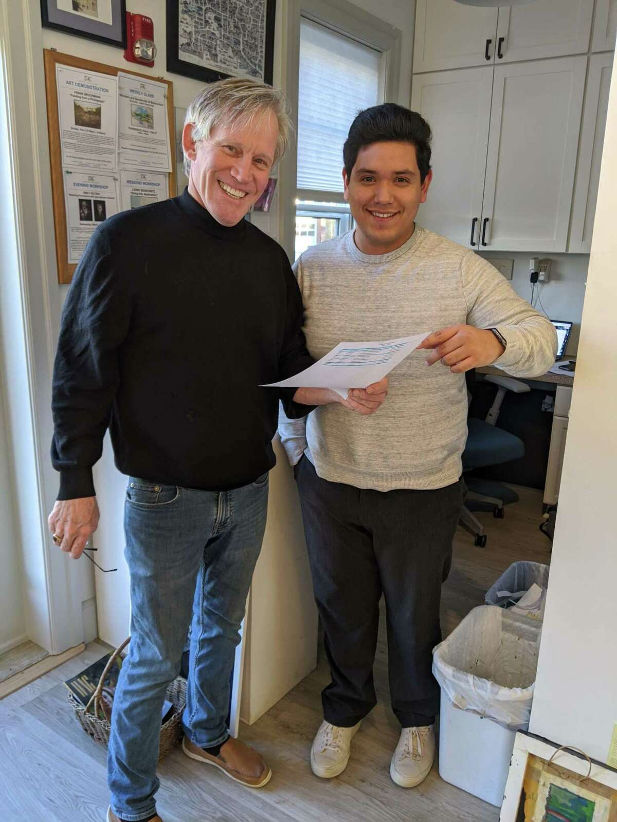 Show chairperson Michael Brennecke reviews the list of volunteers with RAC gallery manager Leo Gonzalez.