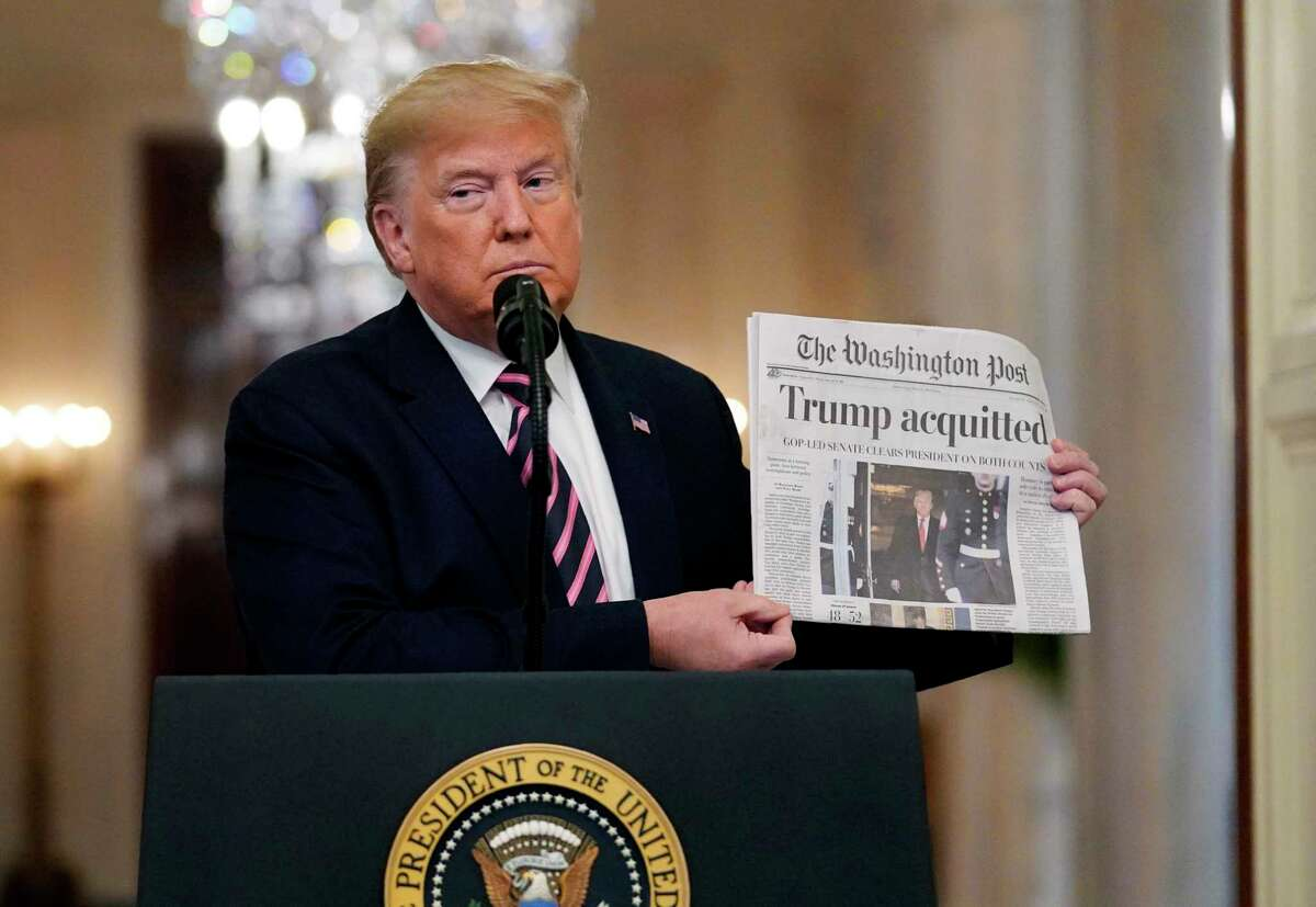 President Donald Trump holds up a newspaper with a headline that reads