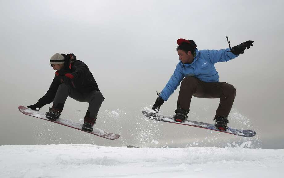 Ahmad Sorush, 22 (left), and Nizaruddin Alizada, 20, snowboard on Kohe Koregh hill on the outskirts of Kabul. They are trying to put the Afghan capital on the winter sports map. Photo: Rahmat Gul / Associated Press