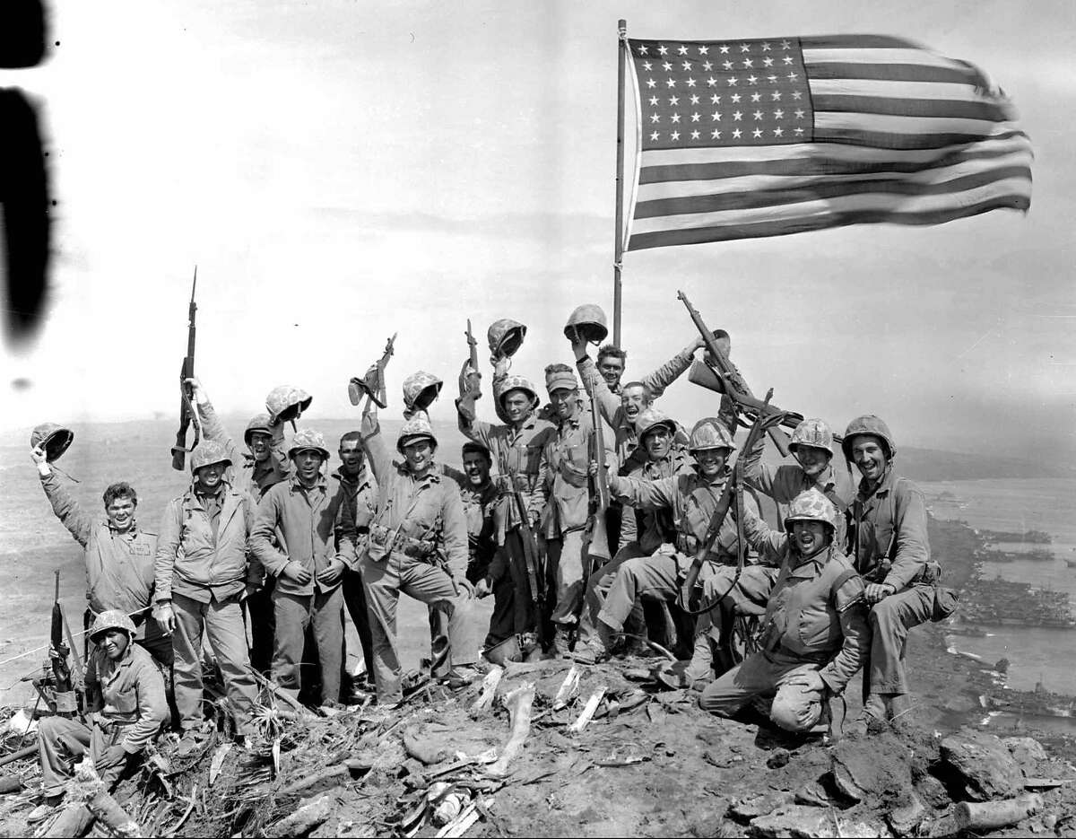 ADVANCE FOR SUNDAY, FEB. 12--FILE--Marines of the 28th Regiment, Fifth division, cheer after raising the American flag at the top of Mount Suribachi, Iwo Jima, on Feb. 23, 1945. AP photographer Joe Rosenthal posed the group shortly after he made his famous flag-raising picture. The dark marks at the upper left are from damage to the original negative.(AP Photo/Joe Rosenthal,File)