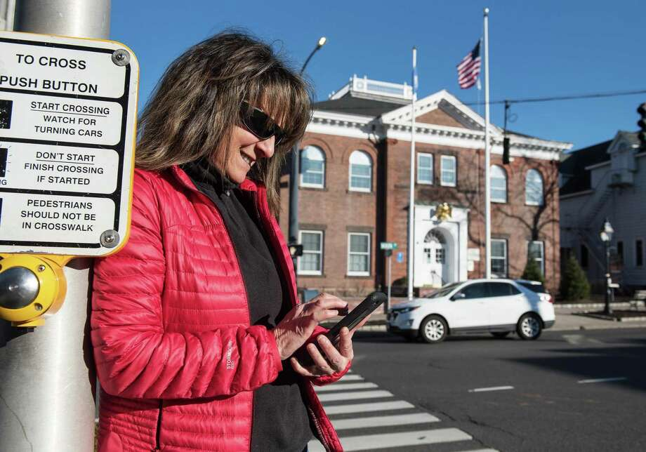 Leslie Costa of Ridgefield checks her cell while walking Main Street, Ridgefield, on Monday, Feb. 3, 2020. The town is considering providing free Wi-Fi in the village area. Photo: Bryan Haeffele / Hearst Connecticut Media / Hearst Connecticut Media
