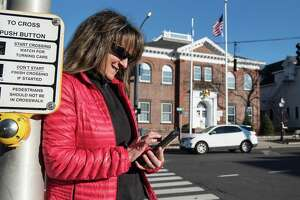Leslie Costa of Ridgefield checks her cell while walking Main Street, Ridgefield, on Monday, Feb. 3, 2020. The town is considering providing free Wi-Fi in the village area.