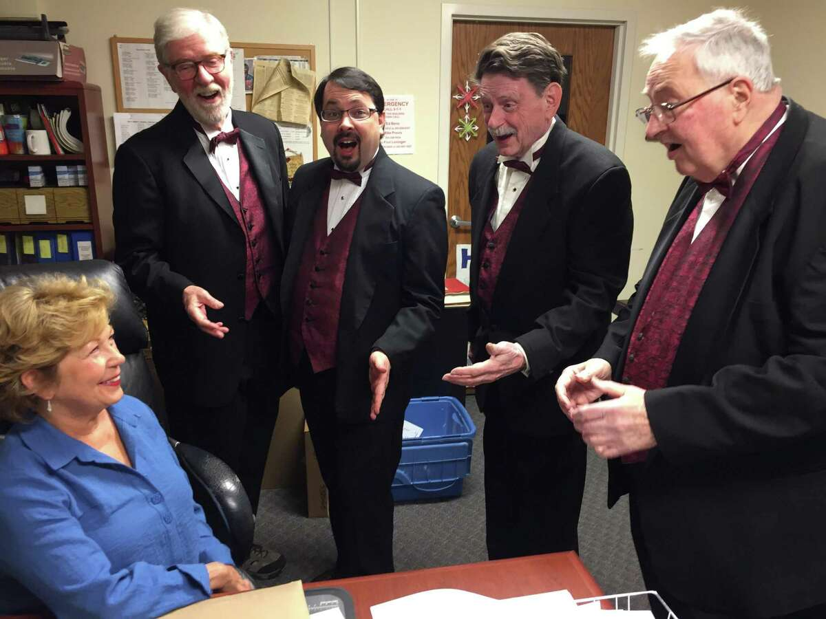 A quartet from the Trumbull-based Coastal Chordsmen serenades Donna Wong of Monroe, preparing for Valentine's Day, Friday, Feb. 14. Quartets will deliver Singing Valentines. A loved one will receive a song plus a chocolate lollipop and rose or a dozen roses. Call 203-816-0462 for more information. Pictured are: Phil Kraft, Darien; Chris Andrade, Fairfield; Richard Allman, Shelton; and Russ Lang, Seymour.