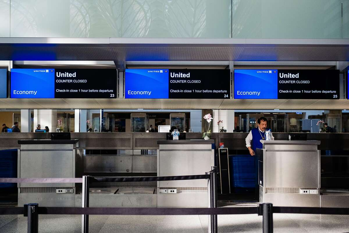 A lone baggage handler stands at empty United Airlines kiosks at the International departures area at San Francisco International Airport in San Francisco, Calif. on Tuesday, February 4, 2020.
