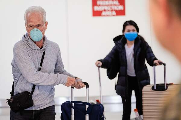 Passengers are seen wearing masks at the International arrivals area at San Francisco International Airport in San Francisco, Calif. on Tuesday, February 4, 2020.