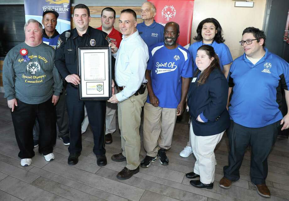 Lt. Dave Hartman, left, and Lt. Rob Kluk of the Wilton Police Department are joined by Special Olympics athletes prior to their leaving to ascend Mt. Kilimanjaro on behalf of the organization. The lieutenants leave Feb. 16. Photo: Contributed Photo / Special Olympics Connecticut / Connecticut Post