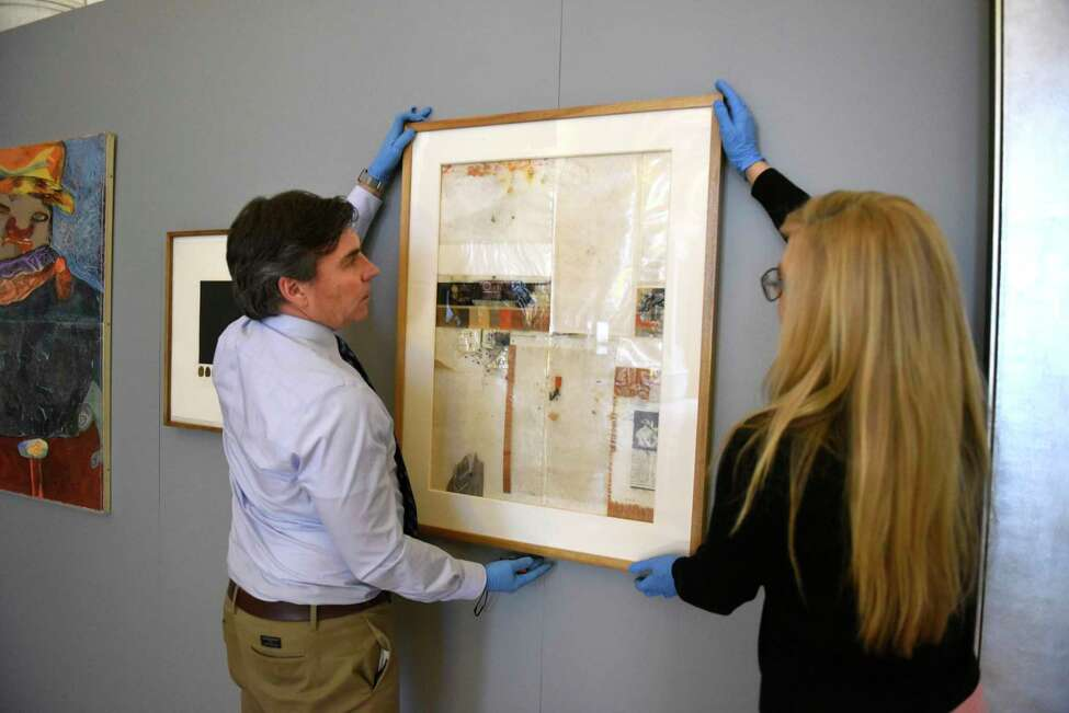 Joe Madeira and Michelle Rosales, both of Office of General Services, hangs a piece of art by artist Jose Urbach titled