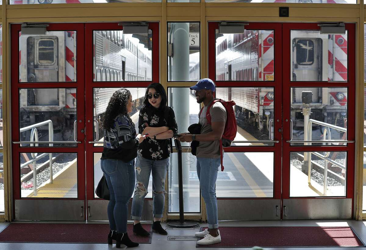 L-R, Nora Abraham, of Washington DC, Shu Li of Salt Lake City, and Miles Campbell of Florida, wait for their train at the Caltrain rail station in San Francisco, Calif., on Sunday, April 22, 2018. A new report for a planned rail extension into downtown would now eliminate the need to demolish the I-280 extension, as previously proposed.