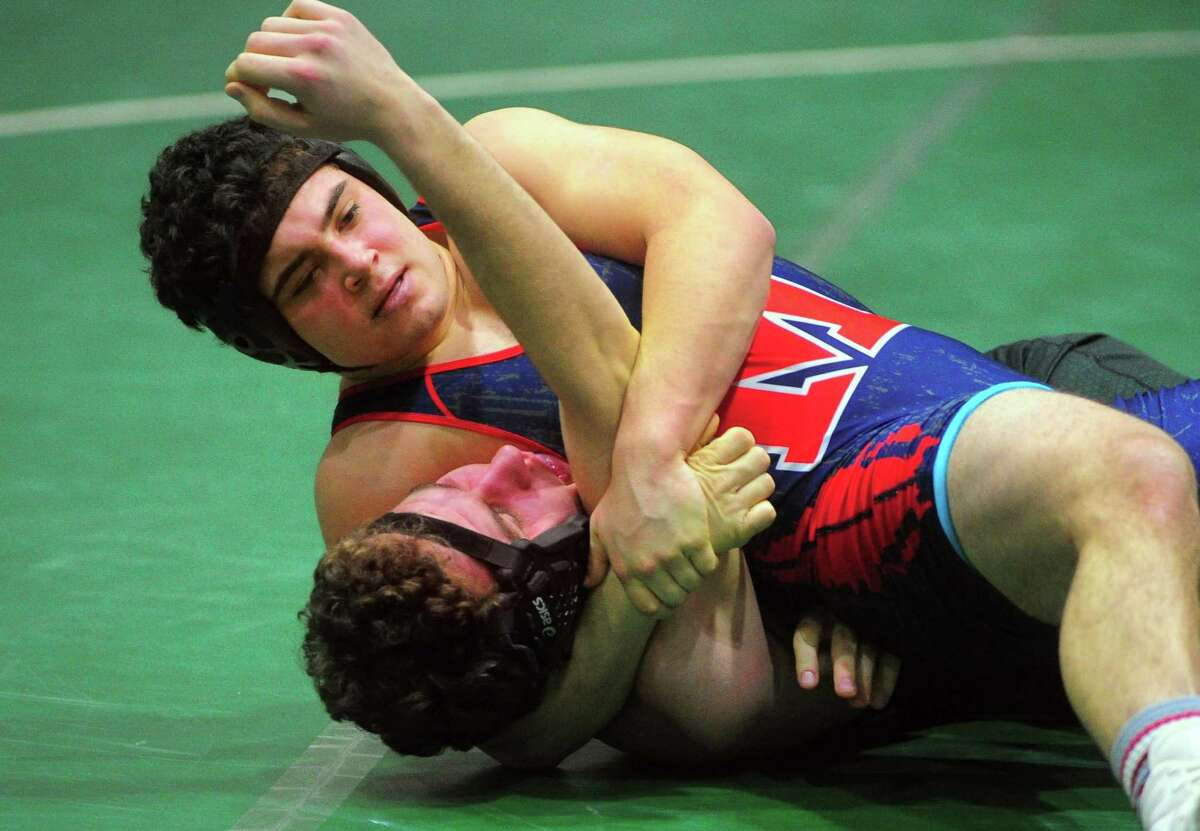 Brien McMahon's Arthur Cocchia works to pin Norwalk's Connor Gilchrist during high school wrestling action in Norwalk, Conn., on Wednesday Feb. 5, 2020. Cocchia and Gilchrist are former members of the Mad Bull Youth Wrestling Club.