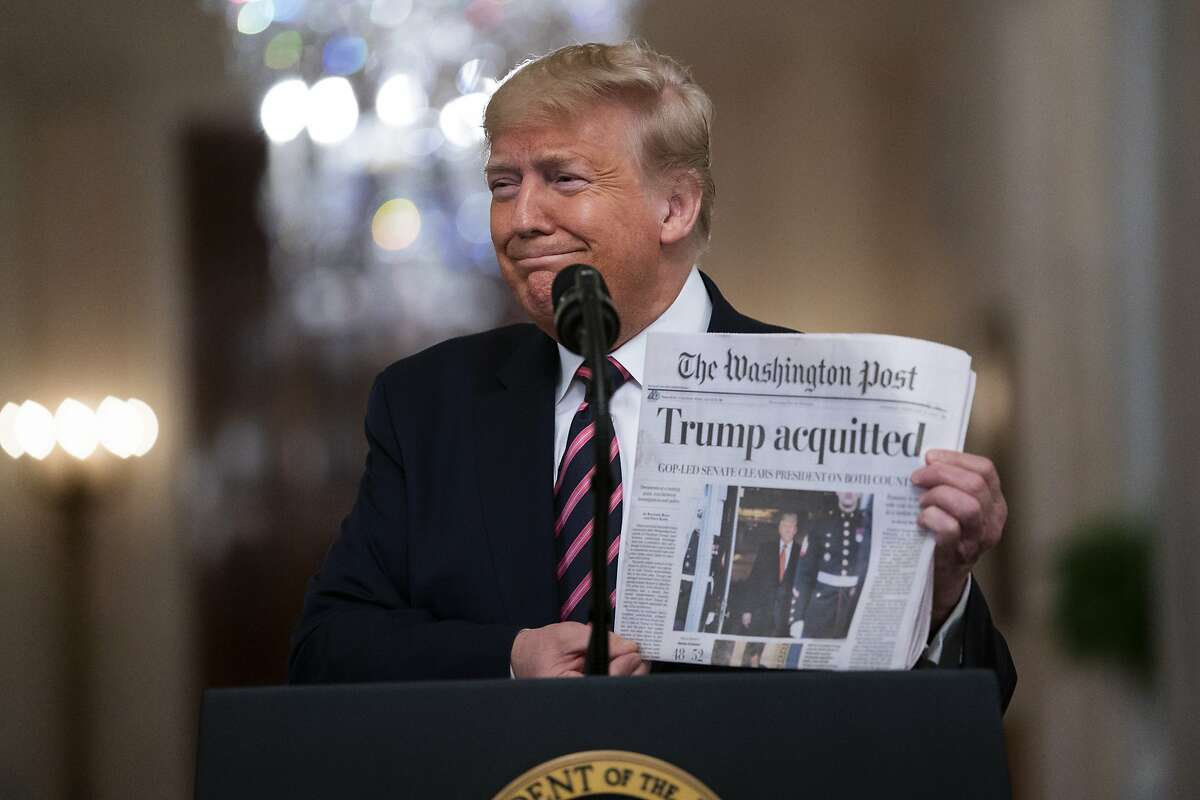 """President Donald Trump holds up a newspaper with a headline that reads """"Trump acquitted"""" as he speaks in the East Room of the White House, Thursday, Feb. 6, 2020, in Washington. (AP Photo/Evan Vucci)"""