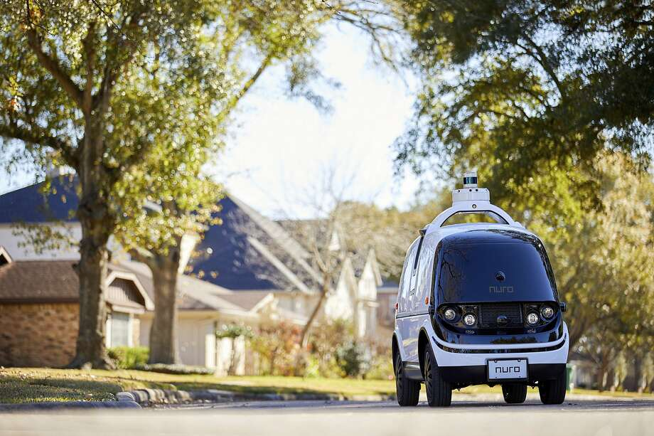A self-driving Nuro heads through a neighborhood street. Below: A man looks over one of the cars, which are designed to make deliveries. The cars now don't need accomodations for human drivers. Photo: Photos By Nathan Lindstrom / Nuro