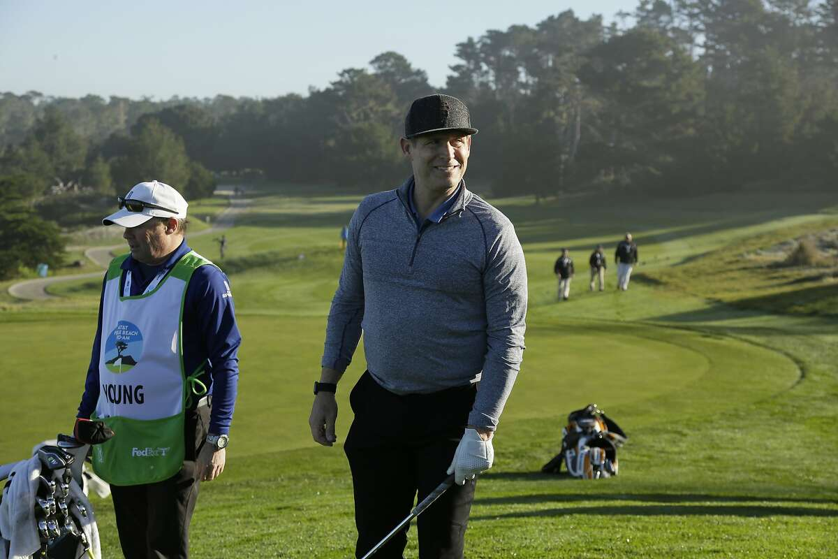 Steve Young visits with fans while waiting to chip onto the second green of the Spyglass Hill Golf Course during the first round of the AT&T Pebble Beach National Pro-Am golf tournament Thursday, Feb. 6, 2020, in Pebble Beach, Calif. (AP Photo/Eric Risberg)