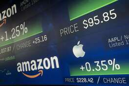 FILE- In this Sept. 4, 2018, file photo Amazon and Apple stock prices are shown on an electronic screen at the Nasdaq MarketSite in New York. According to a January 2020 report by Morgan Stanley strategists, the five biggest U.S. stocks _ Apple, Microsoft, Google's parent company, Amazon and Facebook _ have grown so explosively that they account for nearly 18% of the S&P 500 index by market value, when they make up just 1% of its population. Never before have five companies held such powerful sway over the index. (AP Photo/Mark Lennihan, File)
