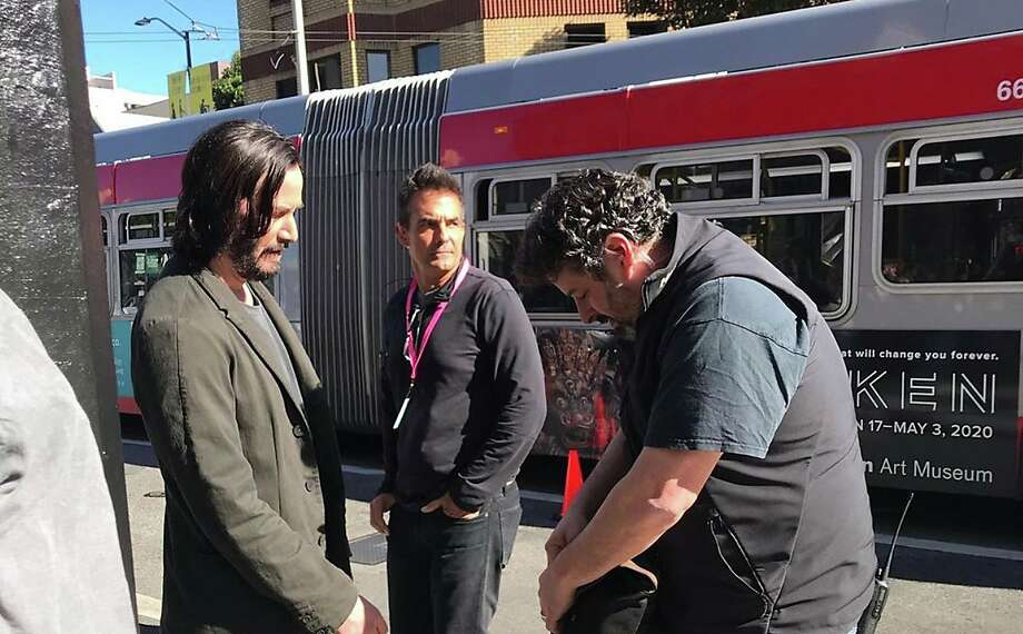 """On Wednesday, Keanu Reeves talks to the camera crew as a Muni bus drives by during filming for """"Matrix 4"""" at Columbus Avenue in North Beach. Photo: Erin Carlson"""