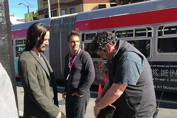"""On Wednesday, Keanu Reeves talks to the camera crew as a Muni bus drives by during filming for """"Matrix 4"""" at Columbus Avenue in North Beach."""