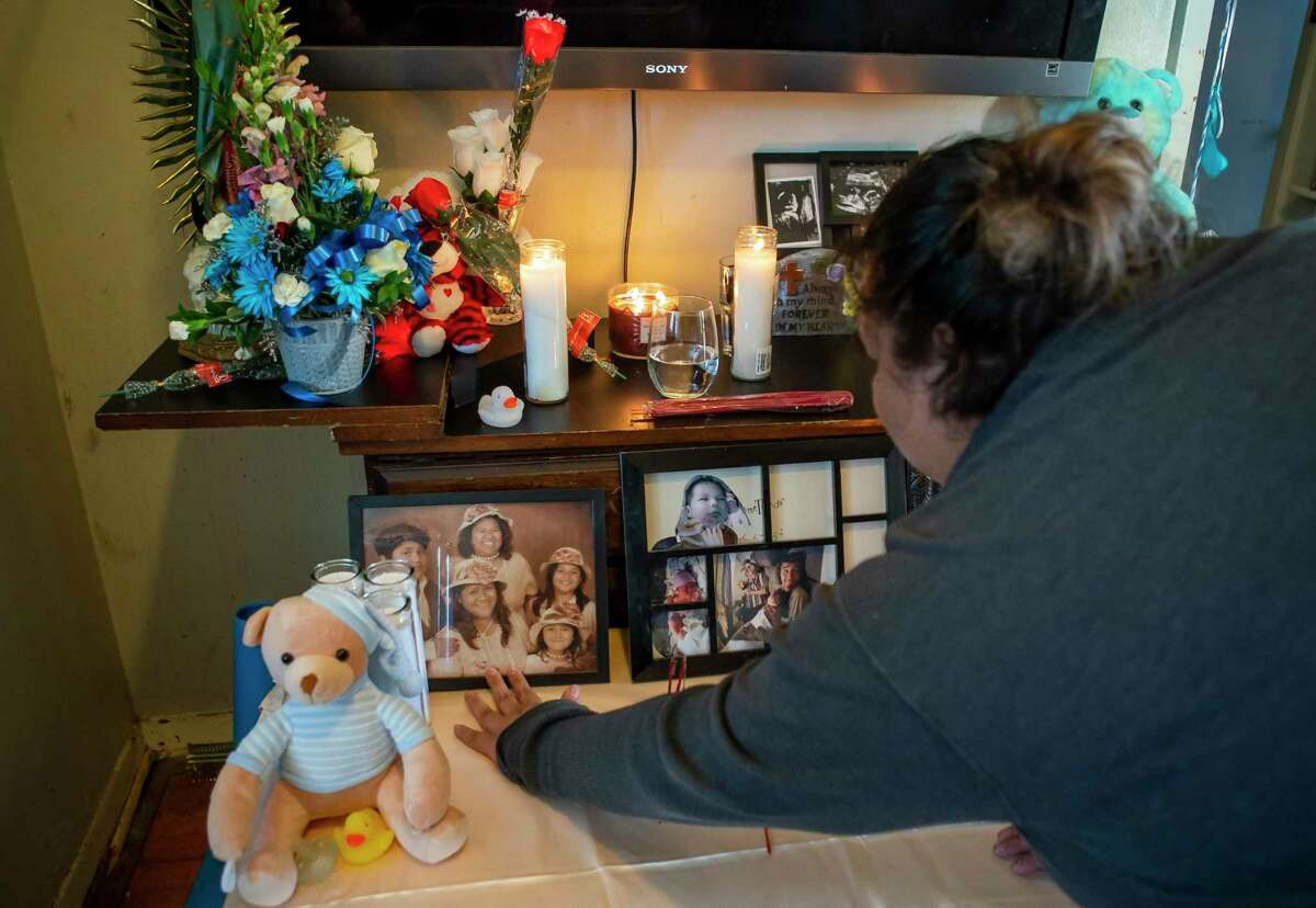 Yesenia Aguilar points out Piedad Romero, who died in a fatal crash Wednesday afternoon in north Houston, in a picture that also includes Piedad's daughter, Diana Soriano-Escobar, who was also killed, and Piedad's youngest daughter, Valeria Soriano, who was injured in the crash, Thursday, Feb. 6, 2020, at the home of Diana Soriano-Escobar and Ricardo Escobar in south Houston. Friends have constructed a temporary altar in the home to honor Piedad, Diana and Diana's infant son, Ricardo Jr., who all died when they were hit by a driver of another car.