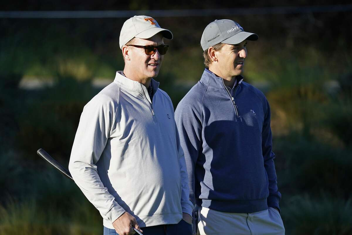 Peyton Manning, left, and his brother Eli Manning wait to hit from the first tee of the Spyglass Hill Golf Course during the first round of the AT&T Pebble Beach National Pro-Am golf tournament Thursday, Feb. 6, 2020, in Pebble Beach, Calif. (AP Photo/Tony Avelar)