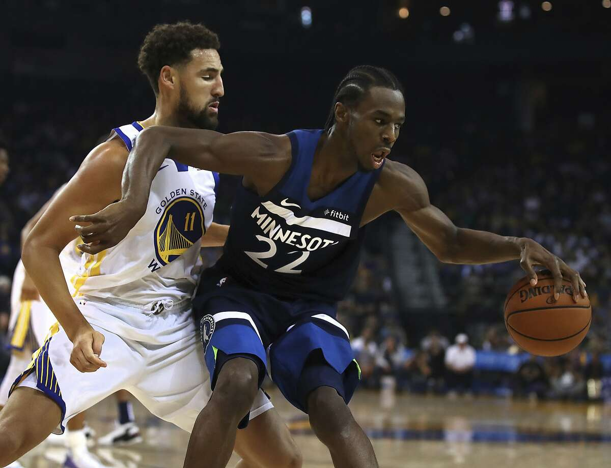 Minnesota Timberwolves' Andrew Wiggins, right, keeps the ball from Golden State Warriors' Klay Thompson (11) during the first half of an NBA preseason basketball game Saturday, Sept. 29, 2018, in Oakland, Calif. (AP Photo/Ben Margot)