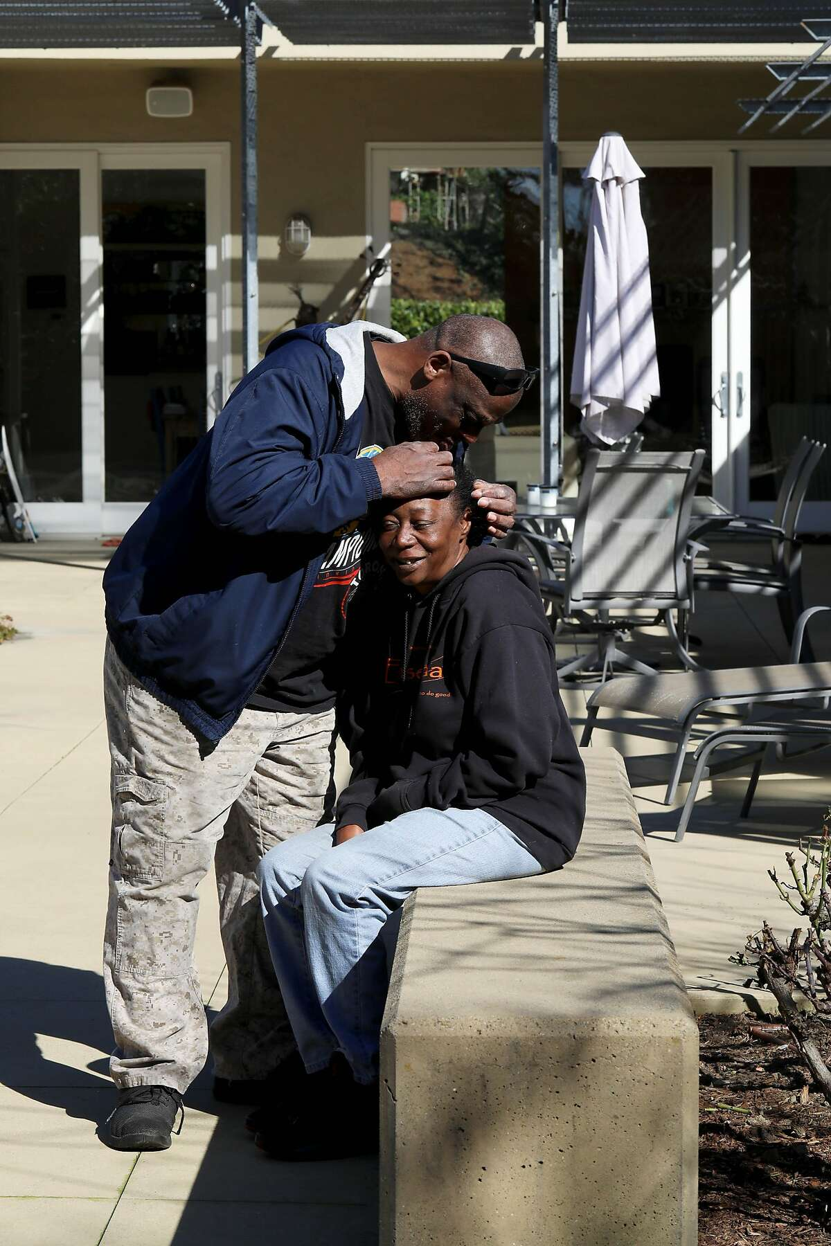 """Greg Dunston touches Marie Mckinzie's head as he searches for her grey hairs as they soak up some rays in the backyard of Terry McGrath's home in Piedmont, Calif., on Wednesday, February 5, 2020. The once homeless couple lived on the streets of Oakland a year ago before McGrath invited them to live in his in-law unit. """"The only thing that's changed is our clothes and today, we're still the same,"""" Dunston said with a smile."""